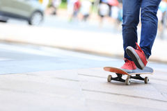 Skateboarder legs riding on skateboard on city Stock Images