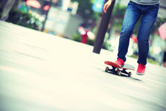 Skateboarder legs riding on skateboard on city Stock Photos
