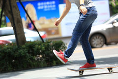 Skateboarder legs riding on skateboard on city Stock Image