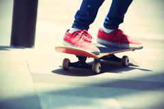 Skateboarder legs riding on skateboard on city Stock Photo