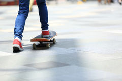 Skateboarder legs riding on skateboard on city Royalty Free Stock Images