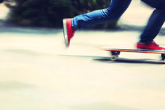 Skateboarder legs riding on skateboard on city Stock Photography