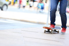 Skateboarder legs riding on skateboard on city Royalty Free Stock Photography
