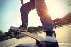 Skateboarder legs riding skateboard stock photo
