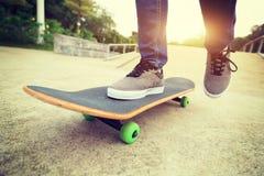 Skateboarder legs riding skateboard Stock Images