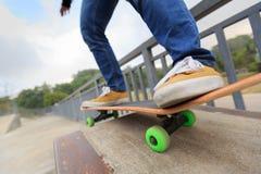 Skateboarder legs skateboarding at skatepark Stock Photography