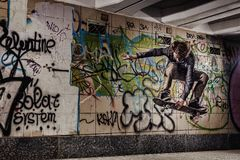 Skateboarder performing grab on graffiti wall background. Skateboarder making grab on graffiti wall in underground passage royalty free stock photo