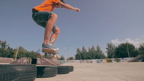 The skateboarder is making tricks, jumping over the wheels. stock video
