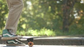 Skateboarder man kicking up skateboard outdoors. Skateboarder does a trick with a skateboard in the park. stock footage