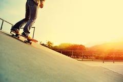 skateboarder met een skateboard rijdend bij stad stock afbeeldingen