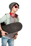 Skateboarder over white background. Cute teen boy wearing stylish hat and glasses listening music, wearing headphones, sportive hobby of a young guy Royalty Free Stock Photography