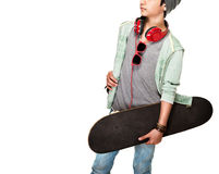 Skateboarder over white background. Teen boy wearing stylish hat and glasses listening music, sportive hobby of a young guy, photo with a copy space Stock Image