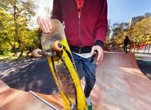 Skateboarder in park halfpipe. Skateboarder holding a skateboard closeup in the park halfpipe Stock Images