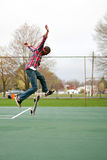 Skateboarder Performing Tricks. A skateboarder performing jumps or ollies on some tennis courts.  Slight motion blur showing the movemant on the arms and legs Royalty Free Stock Images