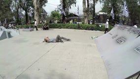 Skateboarder performing tricks fall at Burnham Park, Baguio. Burnham Park, Baguio City, Philippines - April 1, 2016: skateboarder practicing performing acrobatic stock video footage