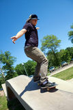 Skateboarder Rail Grinding at. Action shot of a skateboarder performing a rail grind at a skate park Royalty Free Stock Images