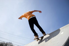 Skateboarder On a Ramp. Action shot of a teenage skateboarder skating down a ramp at the skate park Stock Image