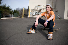 Skateboarder Resting. A young skater resting on his board Stock Images