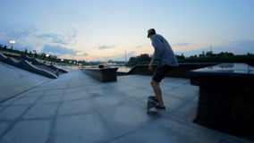 Skateboarder rides and doing tricks on a waterfront in the evening stock video