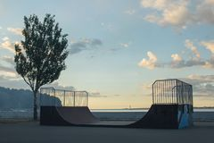 Skateboarder rides on a ramp on a sunset royalty free stock photo