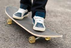 Skateboarder rides on a skateboard feet in sneakers. Stock Photo