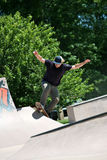 Skateboarder Riding Up a Concrete. Action shot of a skateboarder going up a concrete skateboarding ramp at the skate park. Shallow depth of field Royalty Free Stock Images