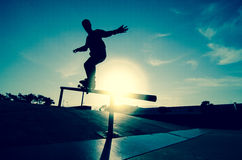 Skateboarder silhouette on a grind. At the local skatepark Stock Photos