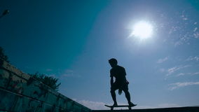 Skateboarder silhouette skateboarding on a sky background at sunset. Slow motion. HD stock video