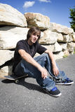 Skateboarder sitting on board Royalty Free Stock Photos