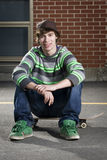Skateboarder sitting on board Stock Photos