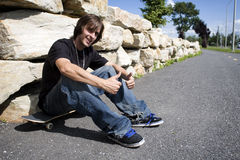 Skateboarder sitting on board in bike path Stock Images