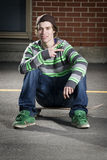 Skateboarder sitting on his board Royalty Free Stock Image