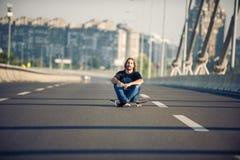 Skateboarder sitting on his skateboard at highway bridge Royalty Free Stock Image