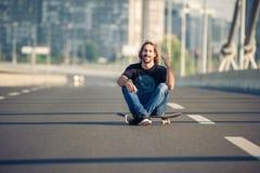 Skateboarder sitting on his skateboard at highway bridge Stock Images