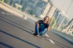 Skateboarder sitting on his skateboard at highway bridge Royalty Free Stock Photography