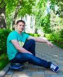 Skateboarder sitting on the skateboard. At skate park Royalty Free Stock Photo