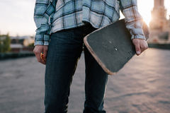 Skateboarder with skateboard. Modern youth. Street subculture for young people, unrecognizable male Royalty Free Stock Photo
