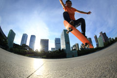 Skateboarder skateboarding at sunrise city Stock Photography