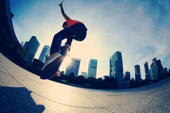 Skateboarder skateboarding at sunrise city Royalty Free Stock Photo