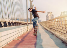 Skateboarder skates and doing jumps over a city bridge. Free rid Royalty Free Stock Photography