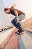 Skateboarder skates and doing jumps over a city bridge. Free rid Stock Photo
