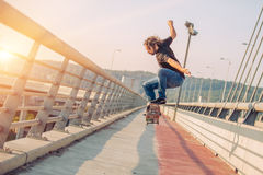 Skateboarder skates and doing jumps over a city bridge. Free rid Stock Photography
