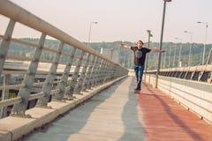 Skateboarder skates over a city bridge. Free ride street skatebo Royalty Free Stock Photos
