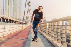 Skateboarder skates over a city bridge. Free ride street skatebo Stock Photos