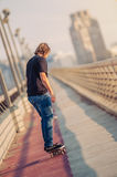 Skateboarder skates over a city bridge. Free ride street skatebo Stock Photo