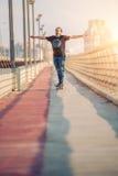 Skateboarder skates over a city bridge. Free ride street skatebo Stock Image