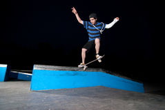 Skateboarder on a slide. At night at the local skatepark Stock Photos