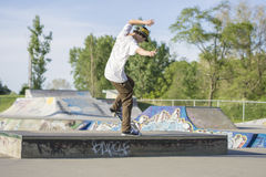 Skateboarder sliding on box  in concrete skate park. Skateboarder sliding on box in concrete skate park during summer Royalty Free Stock Photo