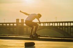 Skateboarder som gör ett ollietrick med att skina för sol som är ljust i bakgrund royaltyfri foto