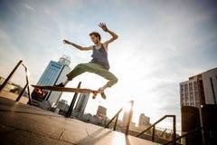 Skateboarder som ombord hoppar mot stadsbyggnader på sommar D arkivfoton